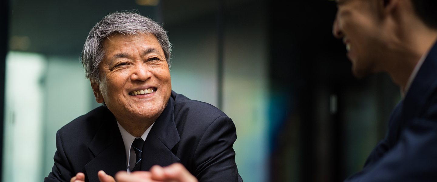 An older Asian man smiling